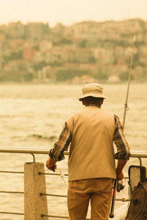 Man Holding a Fishing Rod Near the River