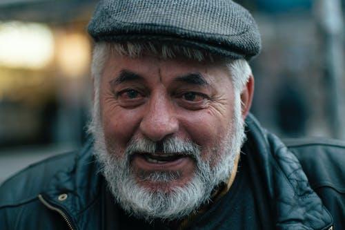 Man Wearing Black Jacket and Flat Cap Smiling