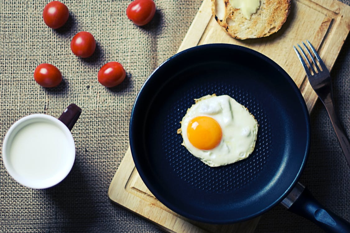 Fried Egg in Frying Pan Beside Mug