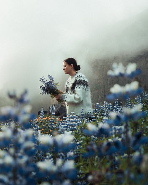 Man in White and Black Long Sleeve Shirt Standing on Blue Flower Field