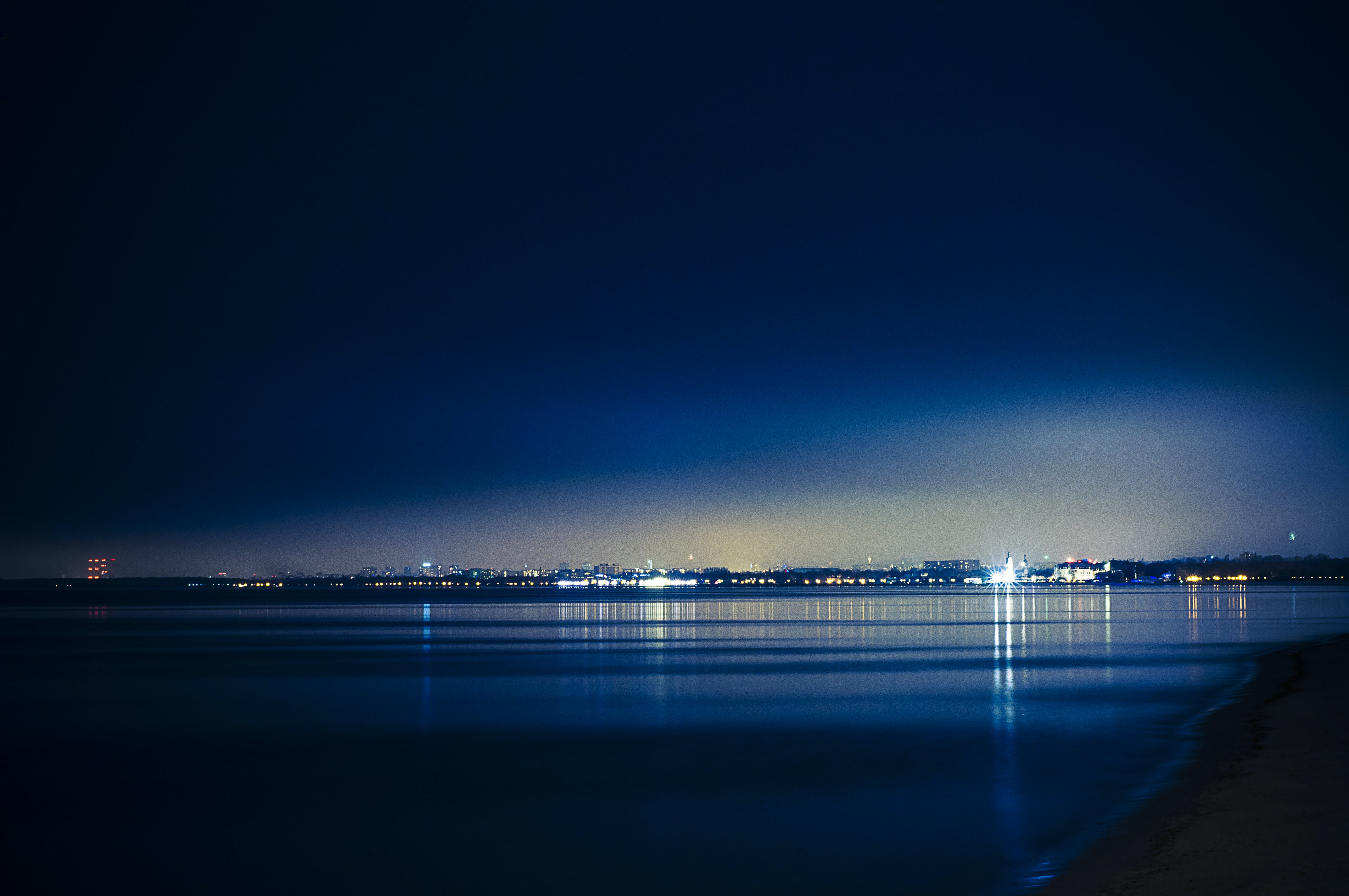 Landscape Photography of Buildings in Front of Calm Body of Water at Nighttime