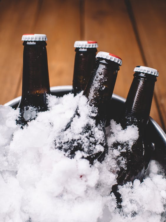 Four Beer Bottles on Gray Metal Bucket Covered With Ice
