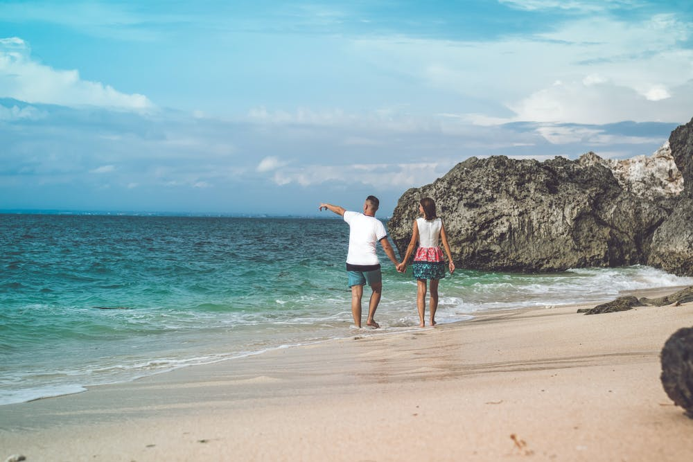 A man and woman walking along the seashore. | Photo: Pexels