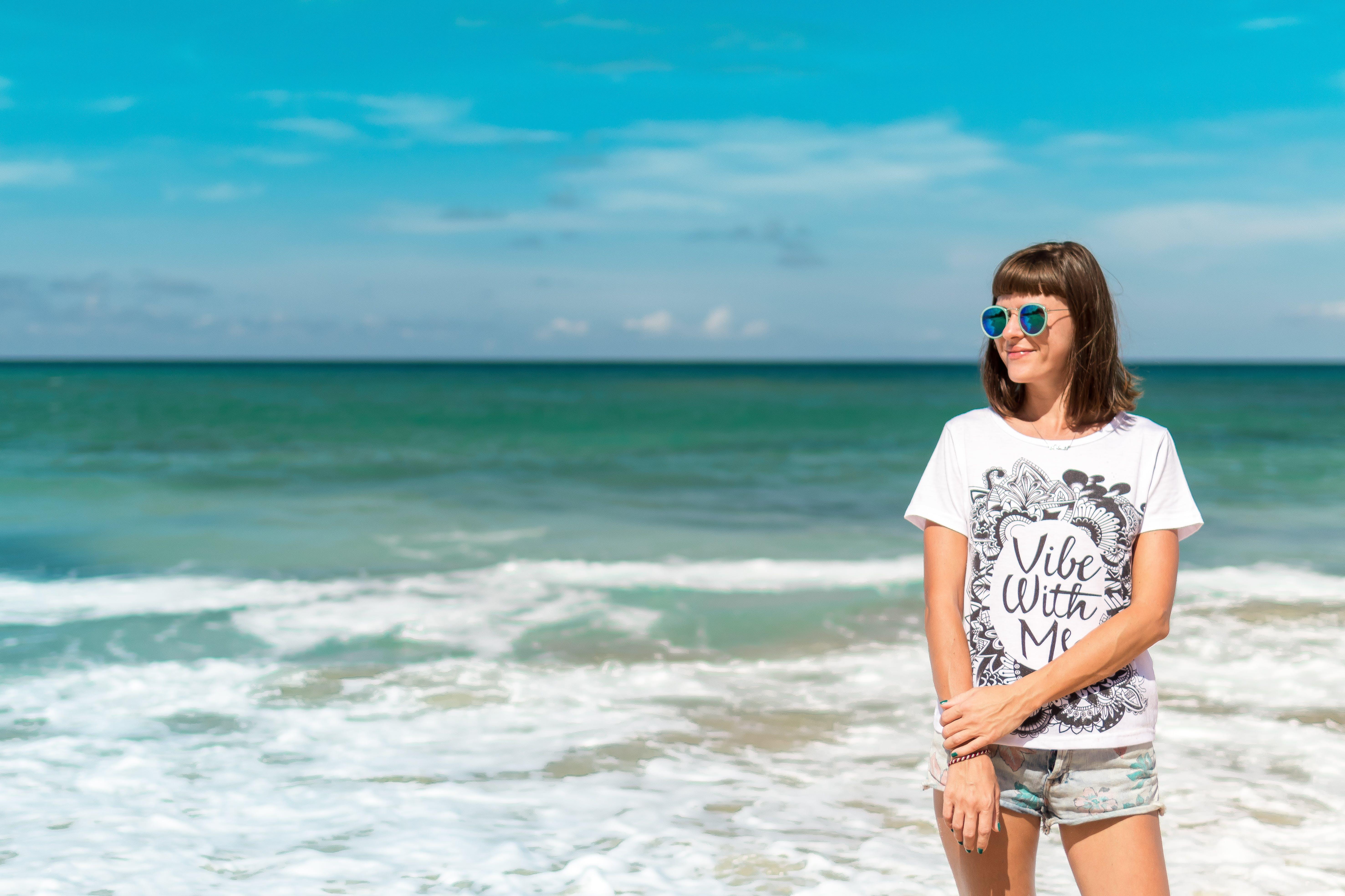 Woman in White Crew-neck Shirt Near Sea Shore