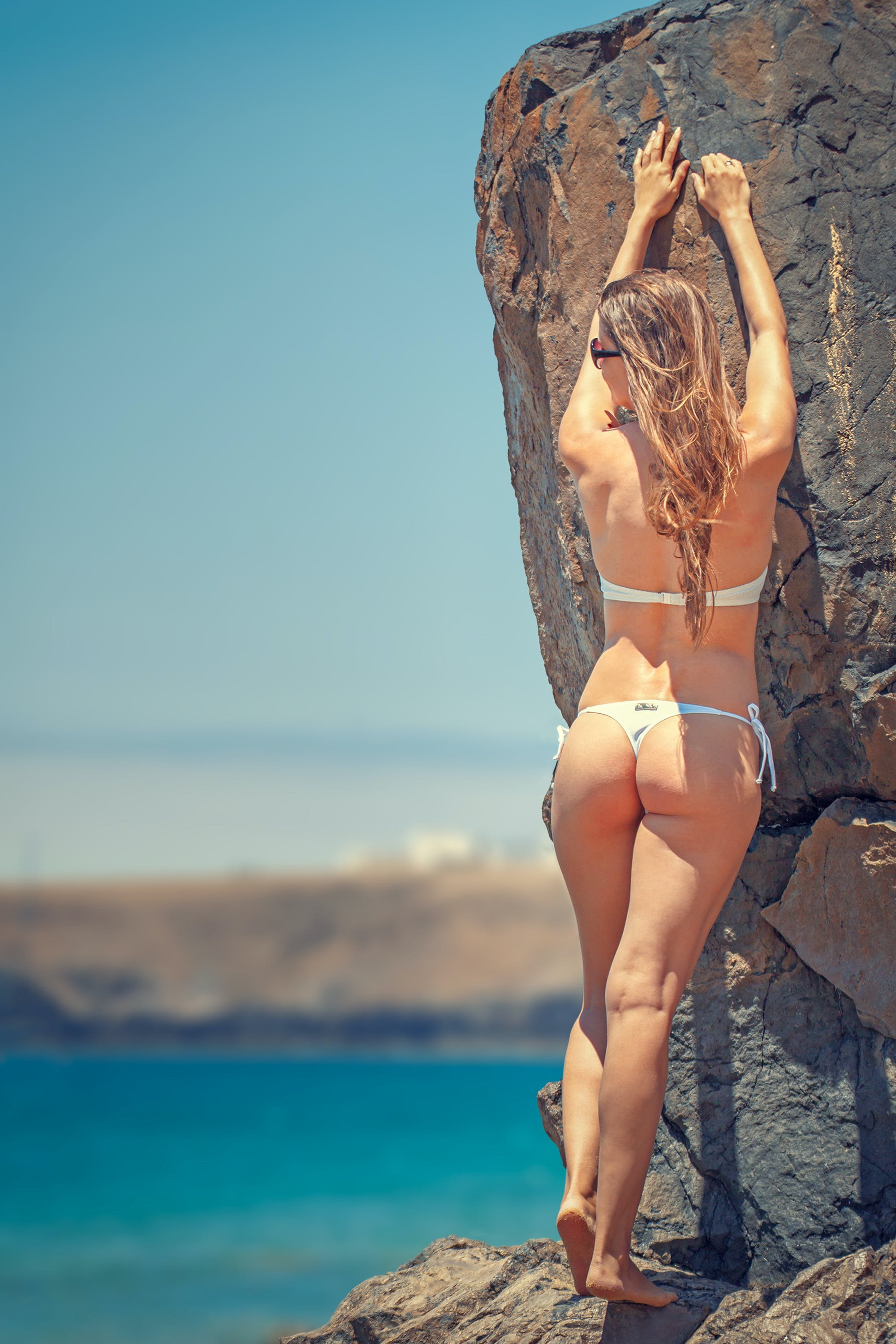 Woman Wearing White Bikini Leaning on Gray Rock