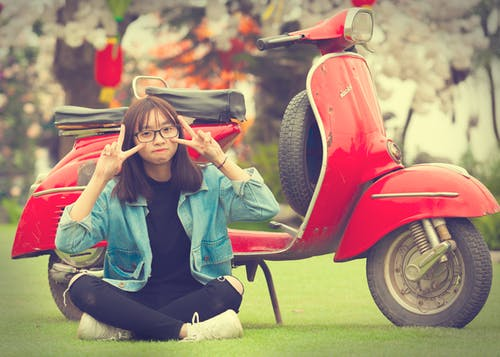 Girl Doing Peace Sign Indian Sitting in Front of Red Scooter Motorcycle