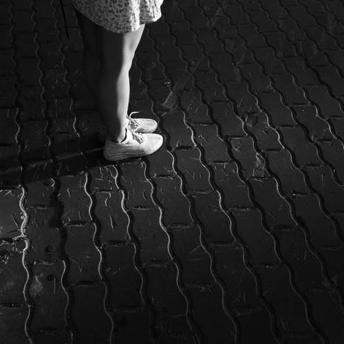 Woman in White Dress Standing on Black Brick Floor