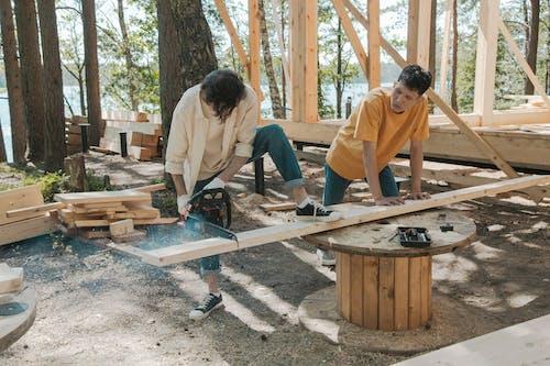 A Man Cutting Wood Plank Using Chainsaw