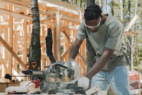 Man Cutting Wood Using Circular Saw