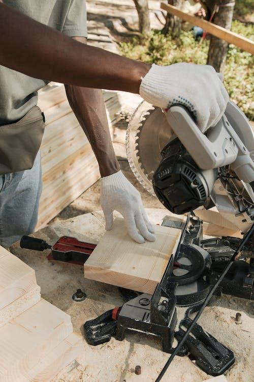 A Person Cutting Wood Using Circular Saw