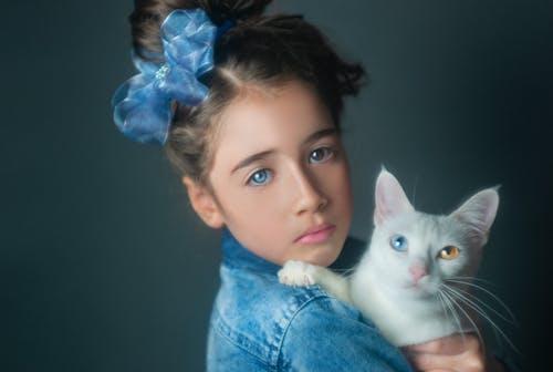 Girl in Blue Denim Jacket Holding White Cat