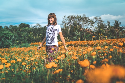 Woman in White and Black Floral Crew-neck T-shirt and Red Bottoms Standing on Orange Petaled Flower Field at Daytime