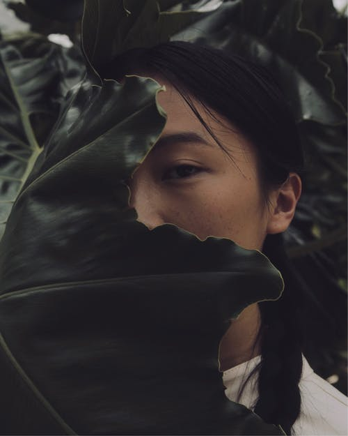 A Woman Covering Her Face with a Leaf