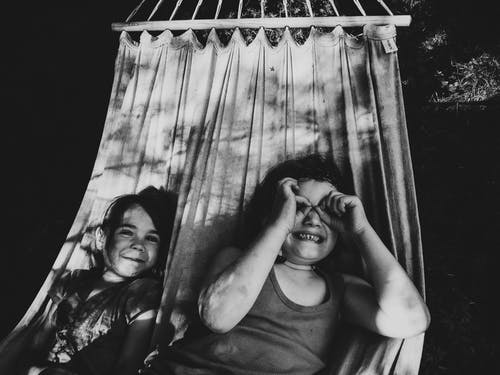Grayscale Photo of Children Lying on a Hammock