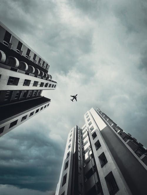 An Airplane Flying Over Skyscrapers