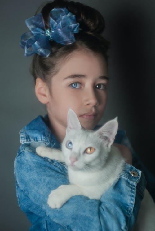 Woman in Blue Denim Jacket Holding White Cat