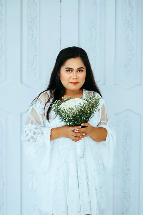 Girl in White Dress Holding Bouquet of Flowers