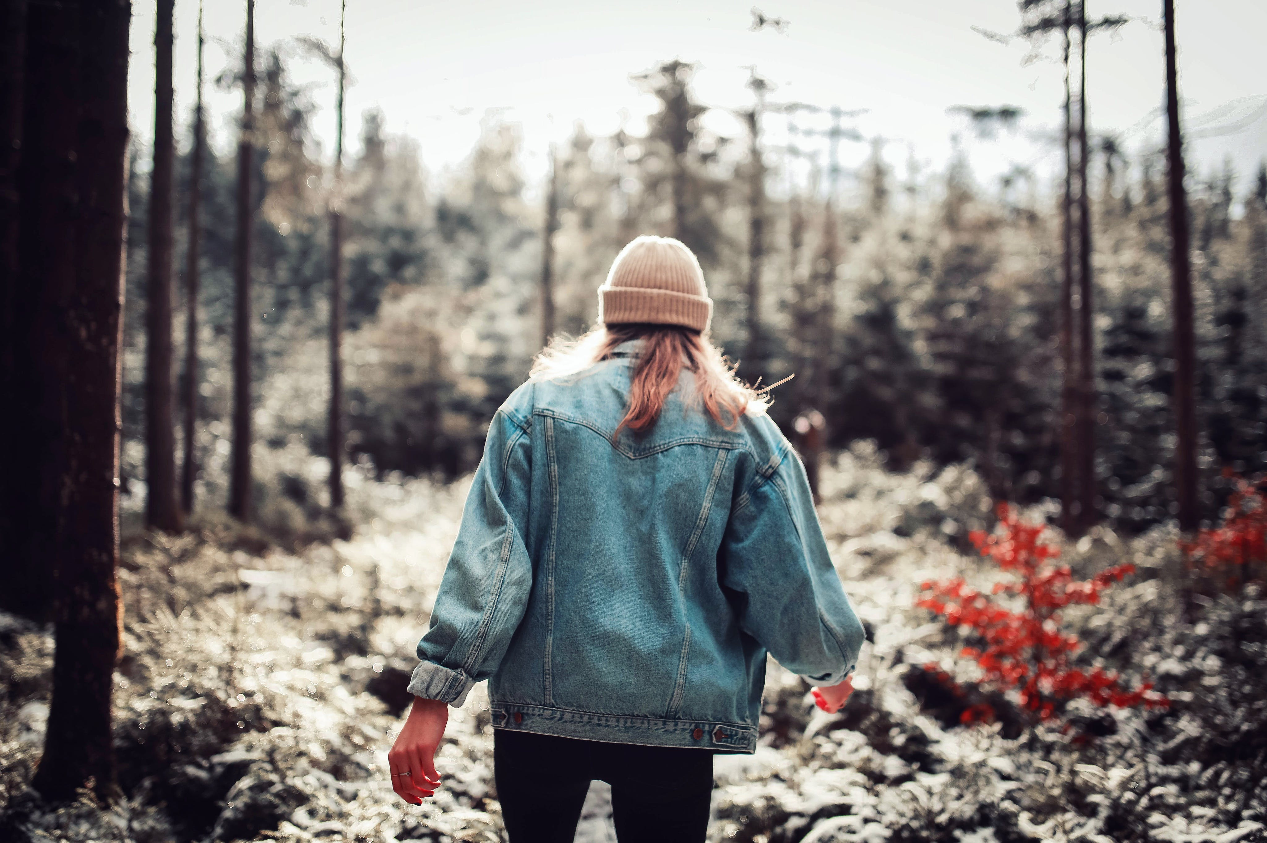 Woman Wearing Blue Denim Jacket and White Beanie Walking in the Forest