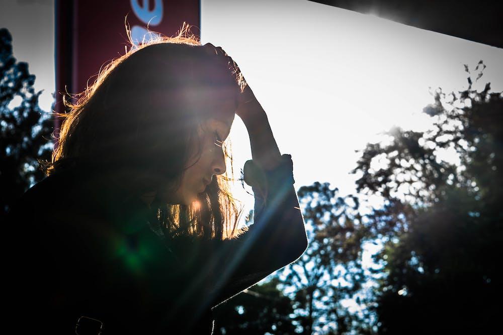 Frau hält ihren Kopf mit der linken Hand. | Quelle: Pexels