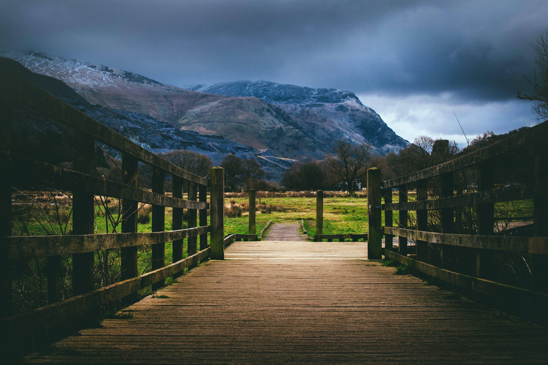 Brown Wooden Bridge Near Mountain at Daytime