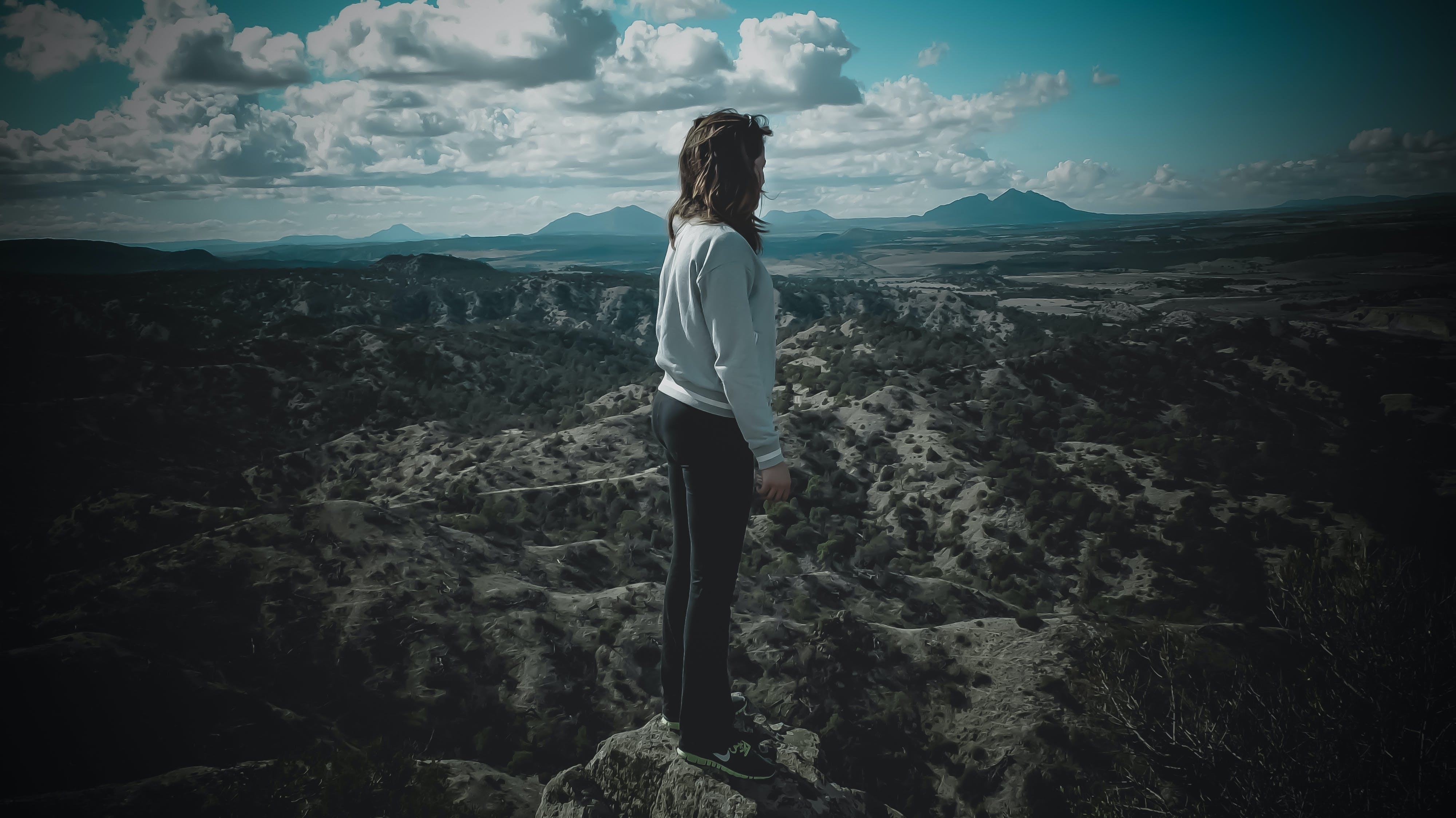 Person in Gray Long-sleeved Shirt Standing on Top of Mountain