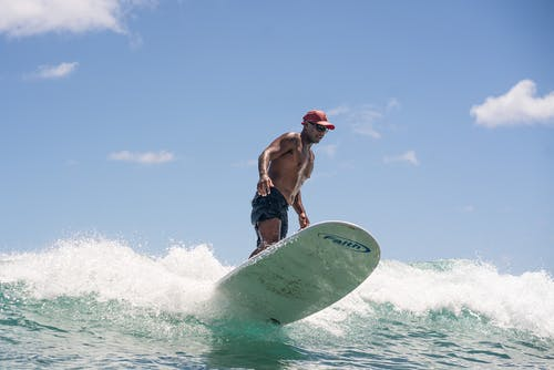 Man in Red Shorts Surfing on Sea