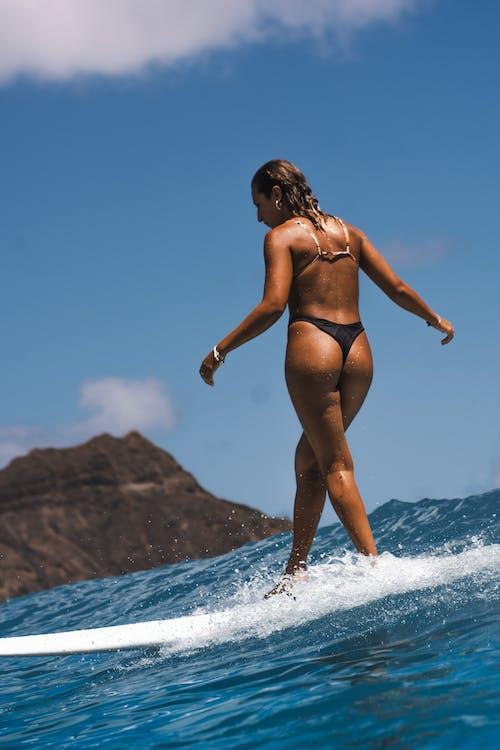 Woman in Black Bikini Standing on White Beach