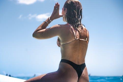 Woman in Black Bikini Bottom Raising Her Hands