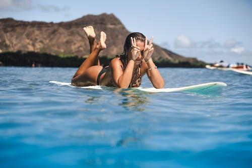 Woman in Black Bikini Lying on Blue Surfboard on Water