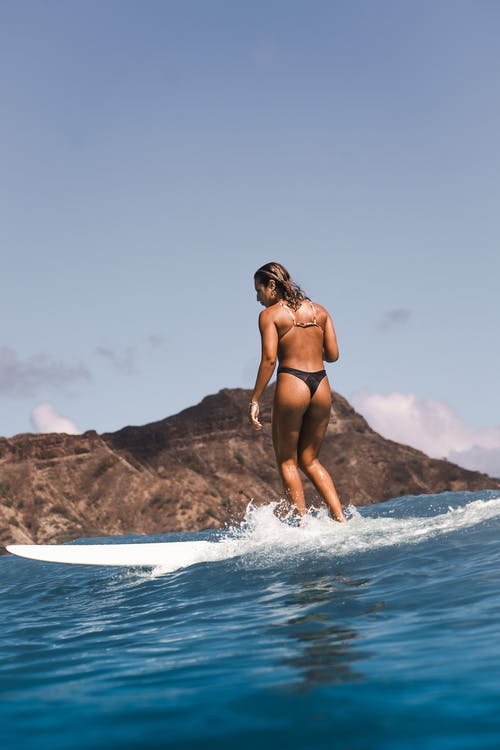Woman in Black Bikini Standing on White Surfboard