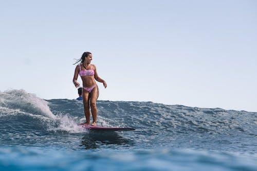 Woman in Pink Bikini Surfing on Sea Waves