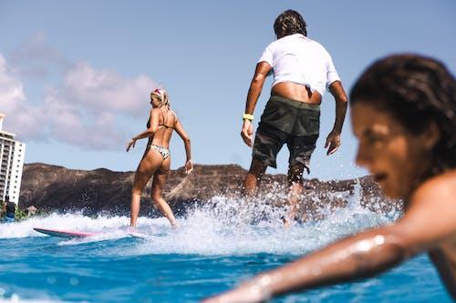 Man in White Shirt and Black Shorts Standing Beside Woman in Black Bikini on Beach during