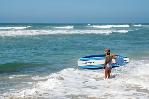 Woman in Blue and White Wetsuit Holding White and Blue Surfboard on Beach
