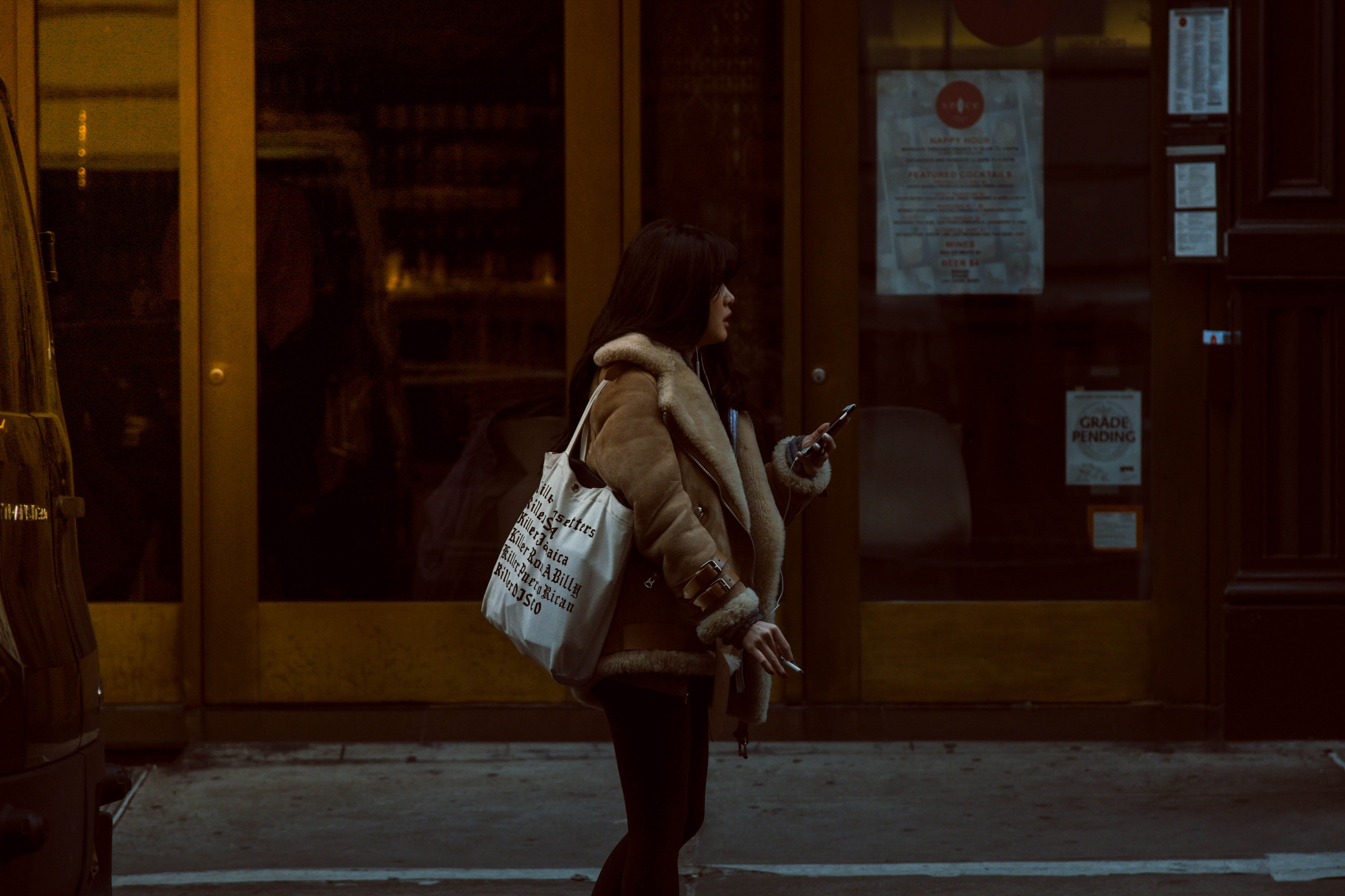 Woman Carrying White Tote Standing Beside Brown Glass Door Building