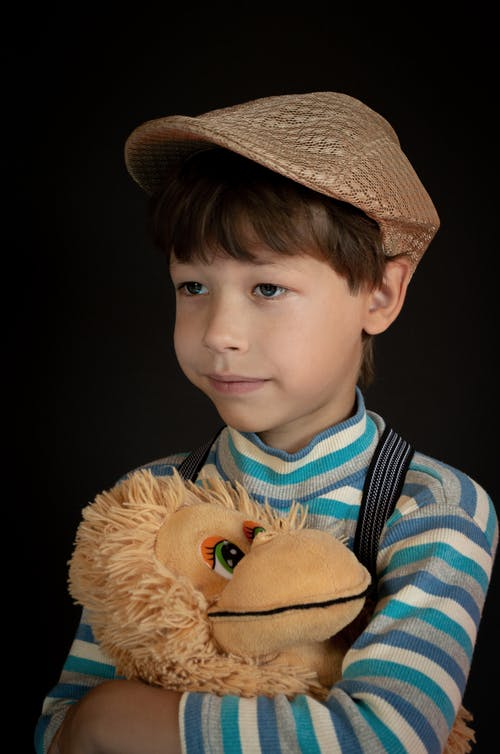 Close-Up Photo of a Boy in a Brown Flat Cap Holding His Stuffed Toy