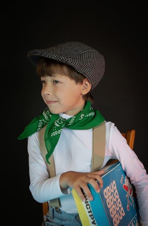 Close-Up Photo of a Boy in a Black Flat Cap Holding a Board Game