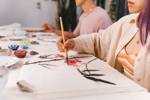 Close-Up View of People Painting