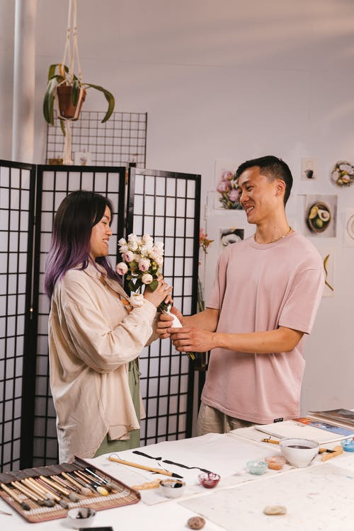 Man Giving His Girlfriend Bouquet of Flowers