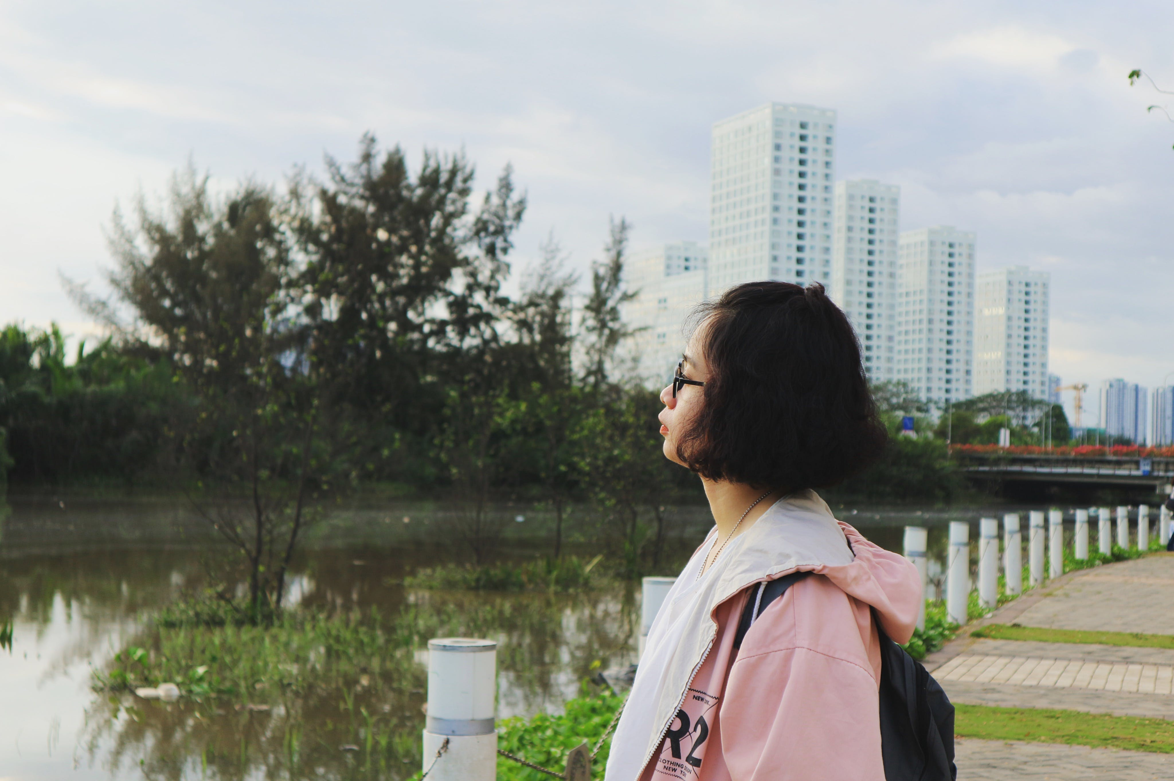 Woman Wearing Pink Hoodie Stand in Front of Body of Water