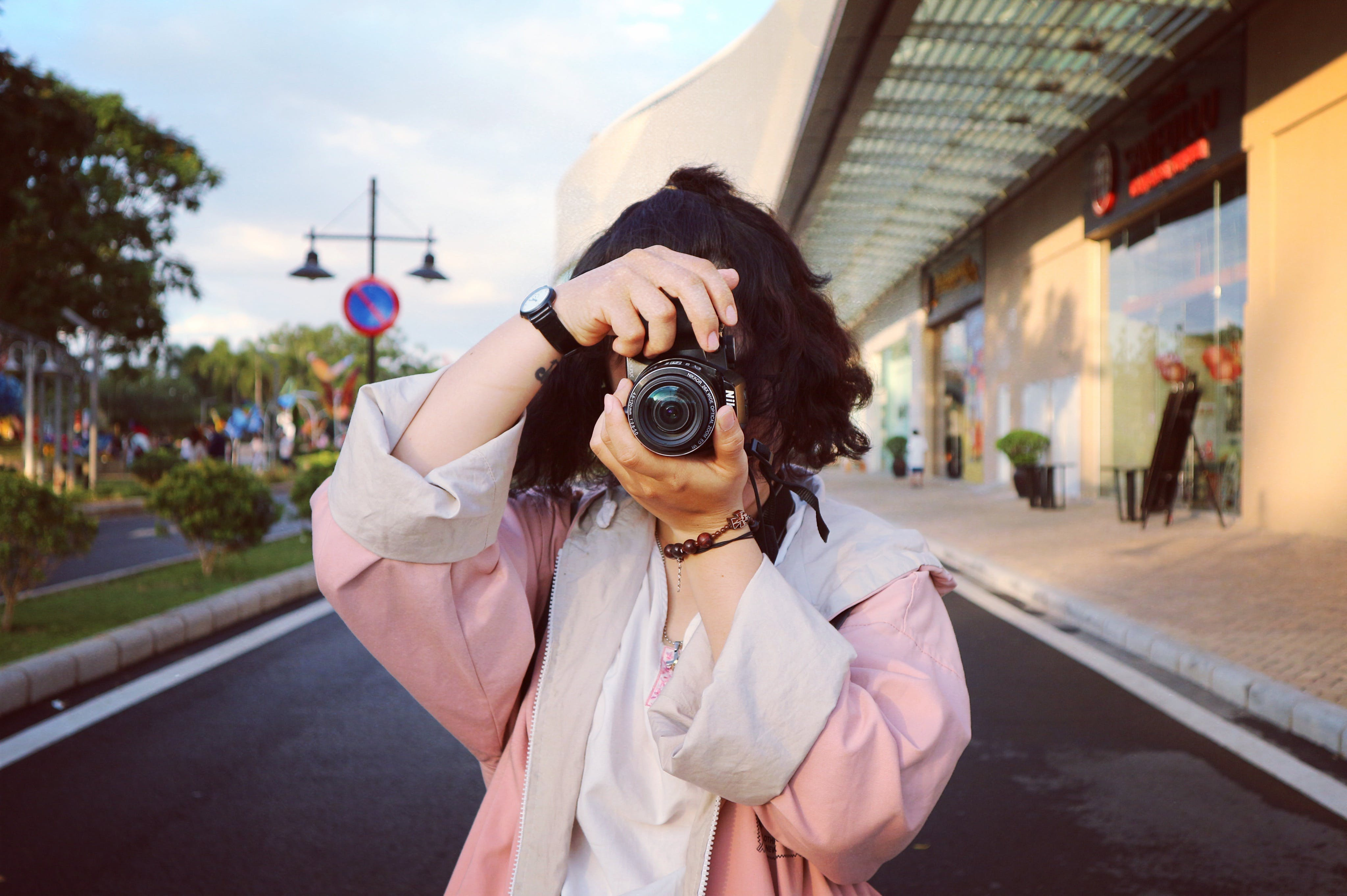 Woman Wearing Pink Coat Holding Dslr Camera