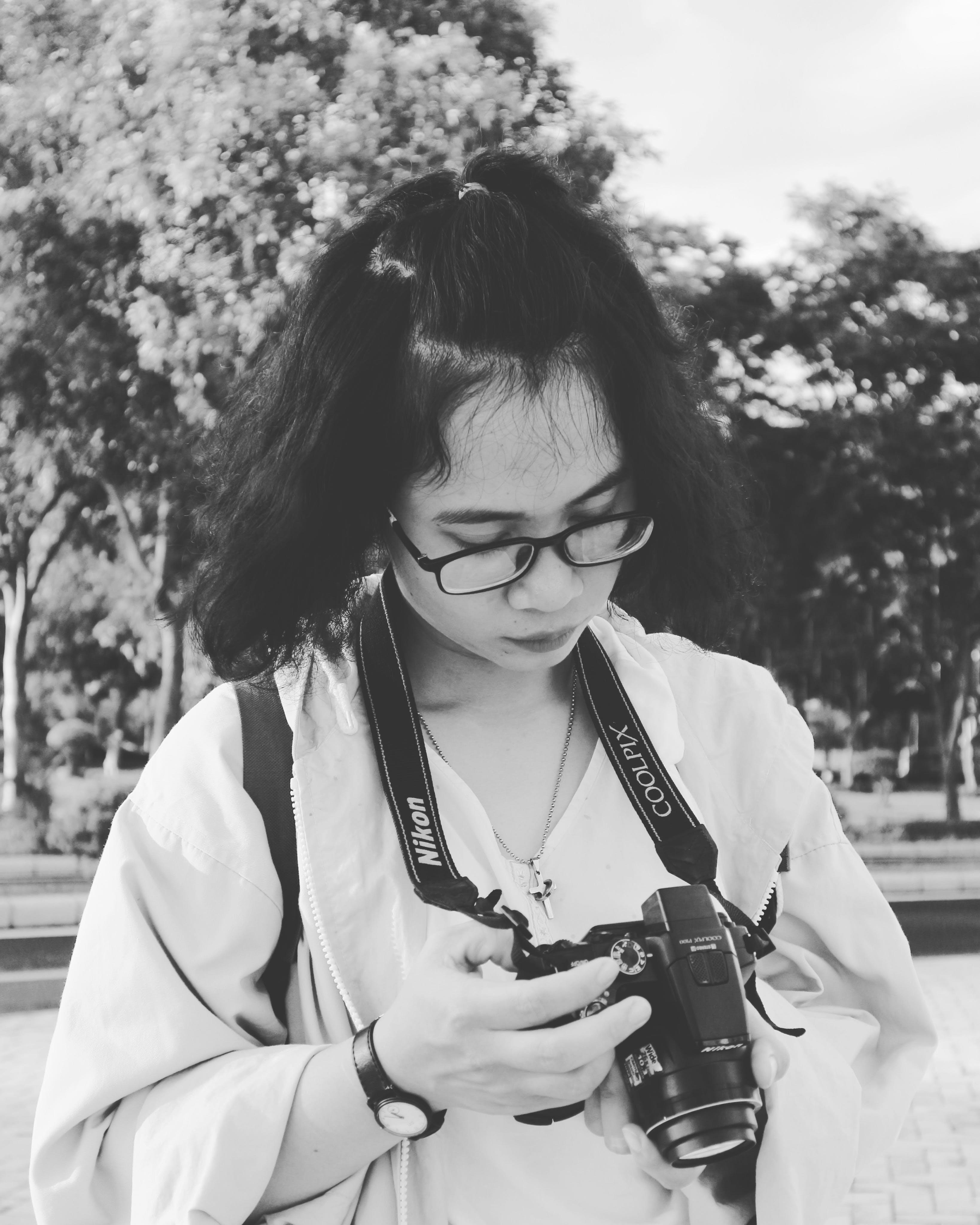 Grayscale Photo of Woman Holding Black Nikon Coolpix Dslr Camera
