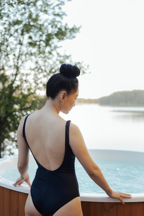 Back View of a Woman in Black Swimwear Standing Near a Jacuzzi