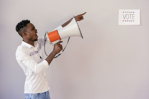 Man Pointing on Vote Signage