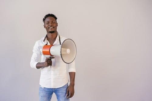 Man in Long Sleeve Short Holding Loudspekaer