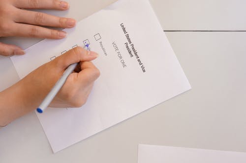 Person Selecting Votes on White Paper