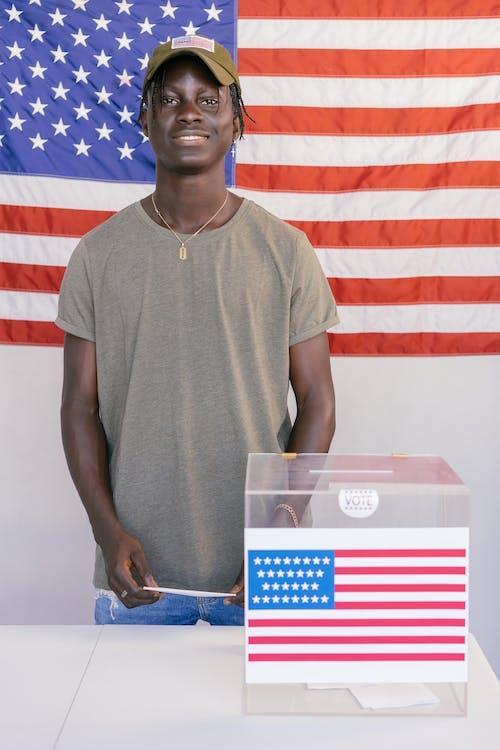 Man Standing Beside Ballot Box