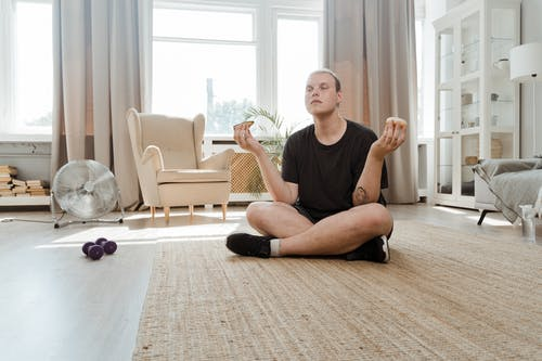 Man With Closed Eyes Sitting on Floor In A Lotus Position
