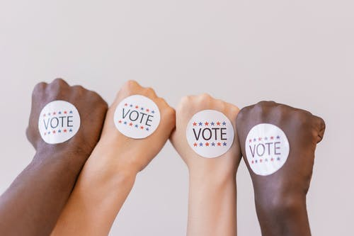 Close Up Photo of Vote stickers on People's Fist