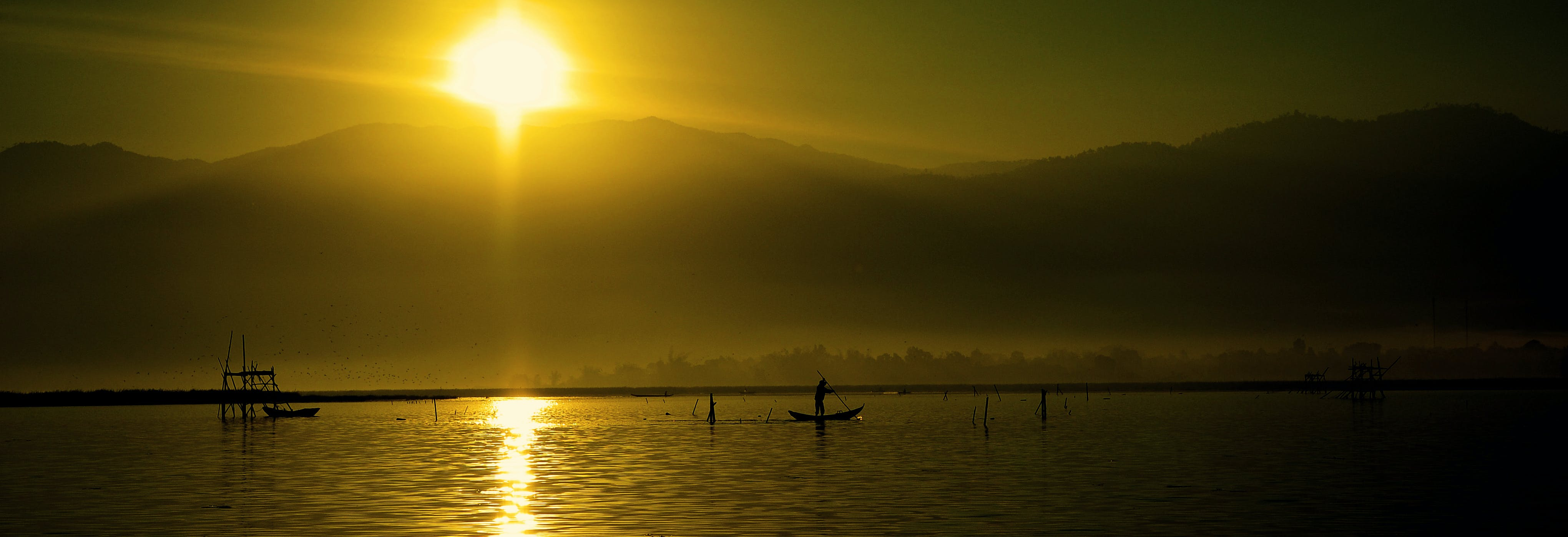 Silhouette of People Riding Boats on Water during Daytime