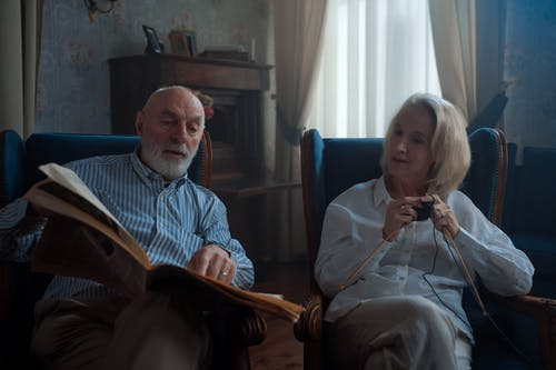 An Elderly Man Reading Newspaper and Woman Knitting While Sitting On Armchairs